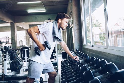 Obraz Wellness men lifting dumbbell weight hand in gym - fototapety do salonu