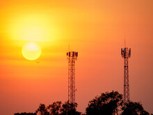 Communication Transmission Towers By Silhouette Of Twilight Sky With Sun The Digital Telephone And Internet Network Signal Transmitter Tower On Sunset Background