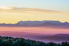 Landscape Of Sierra Morena De Jaen, Located In The Northern Region Of Linares, With Snow-capped Mountains And The Morning Mist Colored By The Sun.