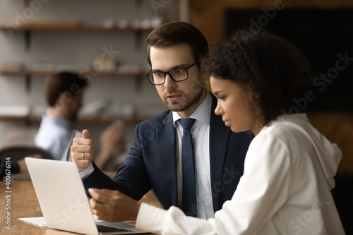 Serious millennial businessman manager expert explain african woman client project details using laptop. Confident young male mentor teach black female colleague instruct student intern at workplace © fizkes