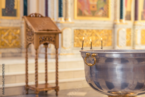 Fotografija Christening ceremony in the Orthodox church, priest lighting candles at children baptismal font, close up