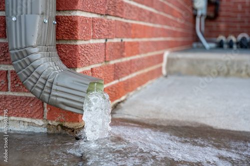 Fototapeta Metal downspout jammed with a frozen ice block