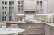 Modern Beige And Grey Colored Kitchen Interior In Classic Style With Dining Table In Luxury Home