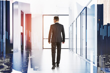 Rear View Of Young Businessman Walking Forward In Office