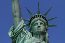 Close Up View Of The Head Of The Statue Of Liberty With The Crown And With The Blue Sky In The Background