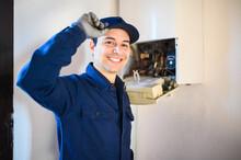 Smiling Technician Repairing An Hot-water Heater