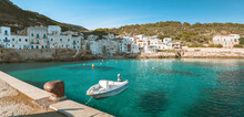 A Fishing Boat Moored In The Port Of A Small Town. Beautiful Crystal Water. Panorama