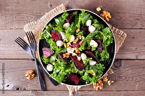 Healthy kale and beet salad with cheese and walnuts. Above view table scene over a rustic wood background. © Jenifoto