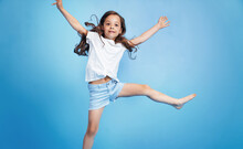 Cheerful Child Jumping In A Blue Room