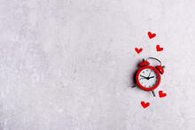 Bright Red Alarm Clock With Hearts On Grey Background With Copy Space