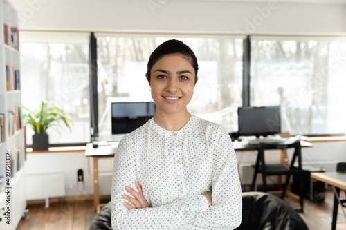 Obraz Confident Indian millennial businesswoman posing with hands folded in office. Head shot portrait of happy young female professional, business leader, boss or corporate coach looking at camera. - fototapety do salonu
