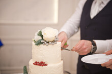 The Hands Of The Groom Cut A White Wedding Cake With Flowers And Berrie