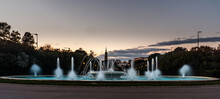 Panoramic Shot Of A Beautiful Fountain On The Background Of Trees And Cloudy Sky