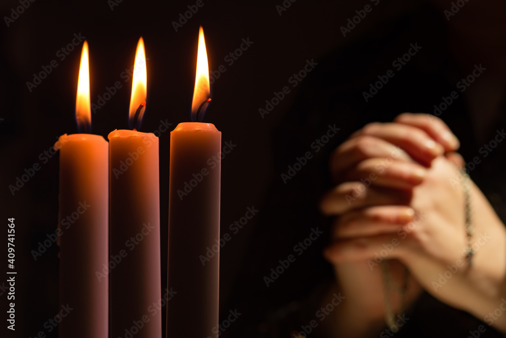 Fototapeta Person prays against the background of lighted candles. Three candles burn against a background of blurred hands clasped in prayer and a crucifix on a chain. Appeal to God. Religion and faith.
