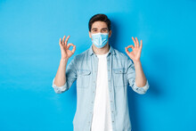 Concept Of Covid-19, Pandemic And Social Distancing. Satisfied Man In Medical Mask, Showing Ok Signs In Approval, Agree Or Like Something Good, Standing Over Blue Background