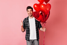 Cheerful Man In Checkered Shirt Holding Valentine Balloons. Studio Shot Of Excited Male Model Isolated On Pink.