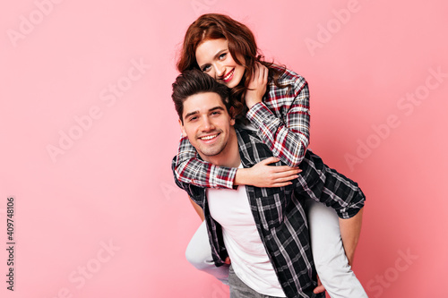 Obraz Adorable girl embracing husband in valentine's day. Studio shot of couple enjoying date. - fototapety do salonu