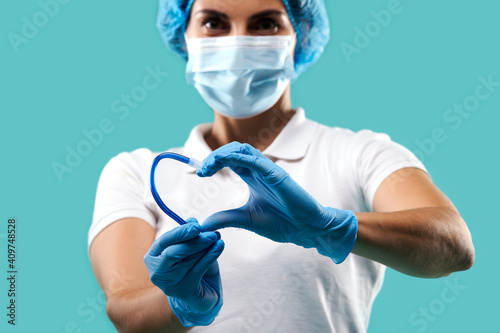 Canvas-taulu Young dentist woman wearing medical uniform holding a saliva ejector and showing a shape of heart
