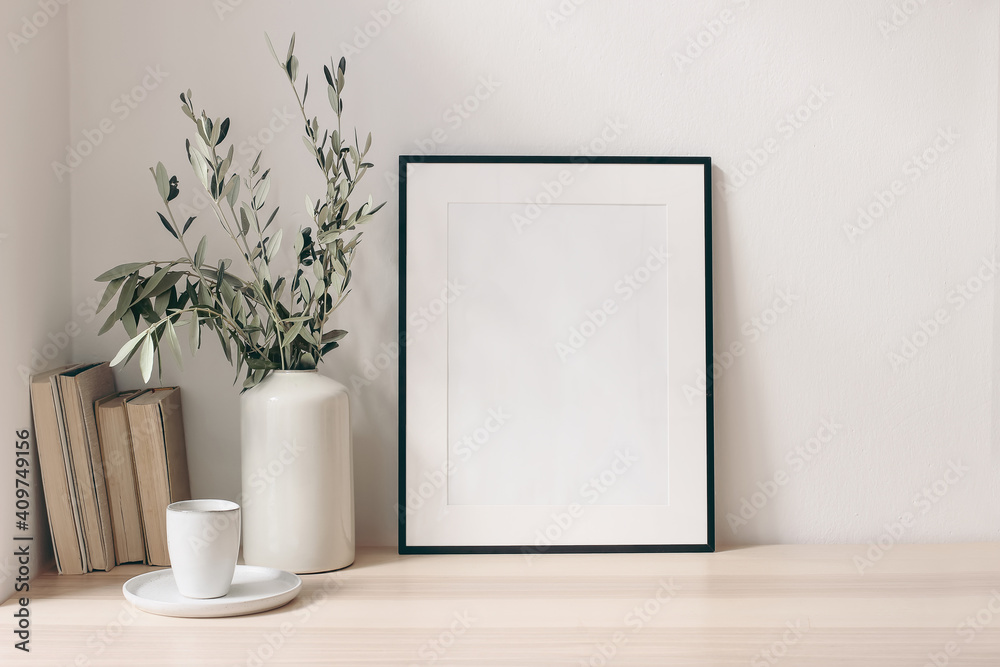 Fototapeta Breakfast still life. Cup of coffee, books and empty picture frame mockup on wooden desk, table. Vase with olive branches. Elegant working space, home office concept. Scandinavian interior design.