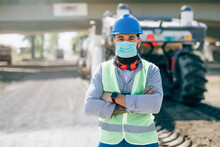 Young Male Road Construction Worker With Face Protective Mask At His Job. Bright Sunny Day. Strong Light.