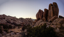 Field Of Boulders At Dusk With Sunset Sky And Crescent Moon In Yucca Valley, California Near Joshua Tree National Park