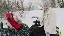Two Young Women Posing With ATV Quad Bike In Winter Forest. Woman Takes Photo Of Her Girlfriend