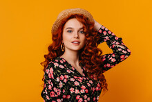 Charming Woman With Long Red Hair Puts On Boater. Photo Of Lady With Massive Gold Earrings Dressed In Beautiful Silk Blouse On Orange Background