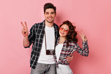 Couple In Love Posing In Checkered Shirts. Studio Shot Of Brunette Man Embracing Girlfriend On Pink Background.