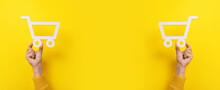 Shopping Cart Symbol In Hands Over Yellow Background, Panoramic Image