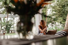 Home Lifestyle Woman Relaxing Enjoying Luxury Sofa Patio Furniture On Outdoor Patio Living Room. Young Woman Sitting On Chair In Green Garden Terrace