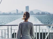 海を眺める女性の後ろ姿