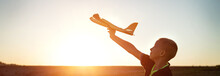 Boy Launches The Plane On A Background Of Sunset Sky