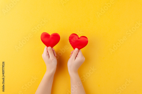 Girl holds in hands red hearts, children arms, love and valentines day concept