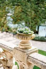 Outdoor Stone Flowerpots With Flowers On A Stone Railing.