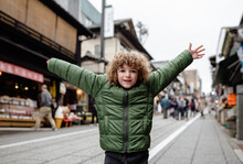 Portrait Of A Happy Young Boy On Vacation, Standing With His Arms Raised In Omotesando Street, Narita City, Japan.