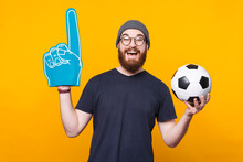 Photo Of A Man Holding A Fan Glove And A Soccer Ball Is Smiling At The Camera .