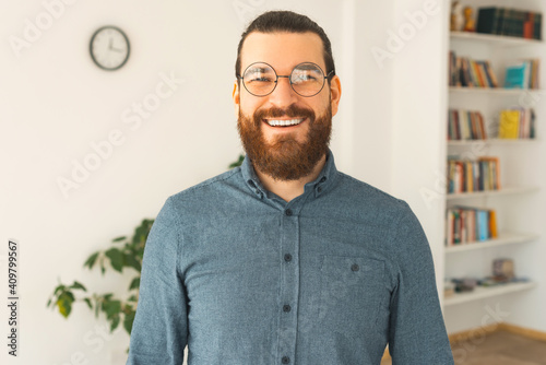 Tela A nice portrait of a young bearded man in a office is smiling at the camera