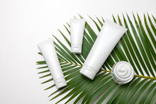 White Cosmetic Tubes And Jar Of Face Cream With Palm Leaf On White Background. Flat Lay.