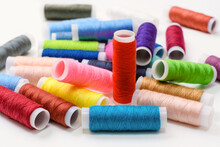 A Pile Of Scattered Spools Of Thread For Sewing. Sewing Hobby Concept. Selective Focusing On The Red Coil.
