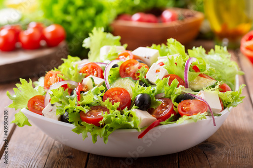 Fototapeta Bowl of fresh salad with vegetables, feta cheese and olives on a wooden table obraz