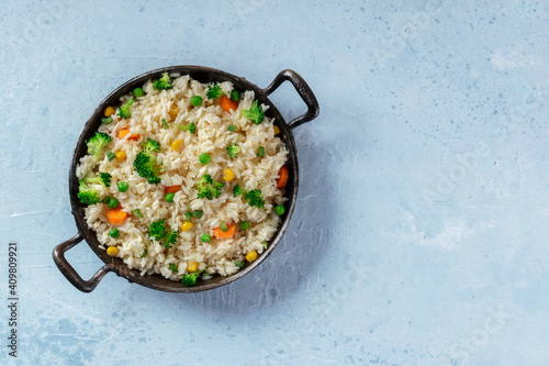 Fototapeta Vegan vegetable rice in a pan, top shot with copy space. Healthy dish with broccoli, green peas and carrots, easy recipe obraz