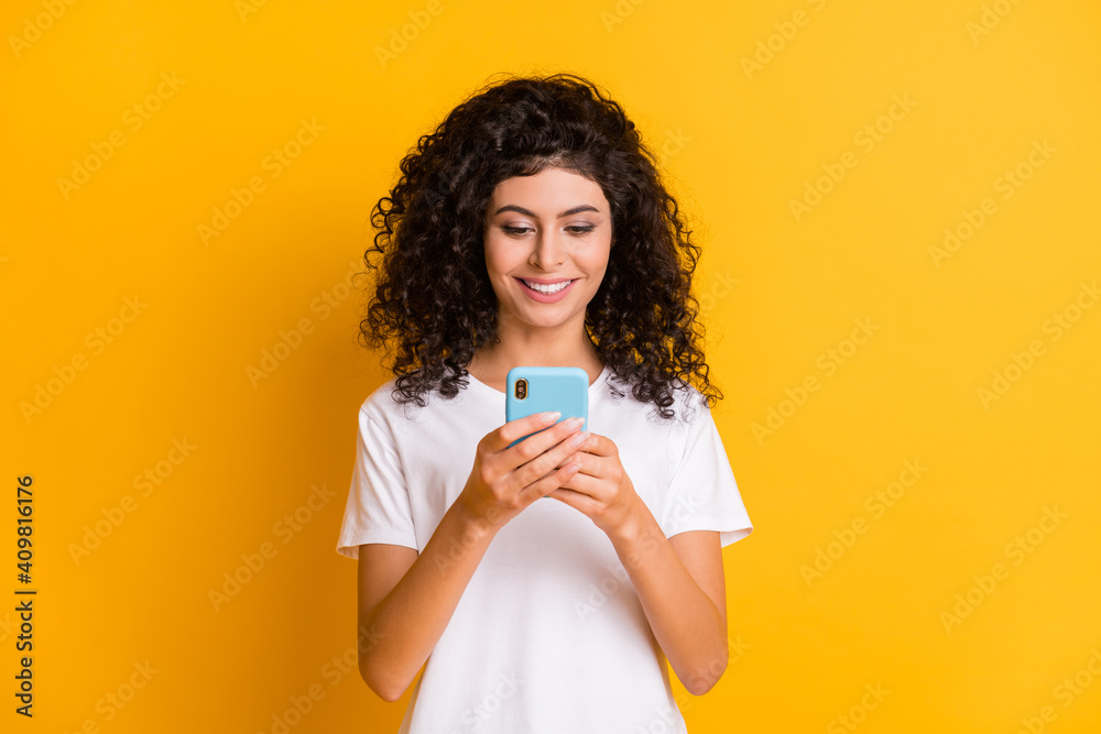 Fototapeta Photo of young happy positive cheerful good mood girl using cellhpone wear white t-shirt isolated on yellow color background