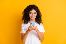 Photo Of Young Happy Positive Cheerful Good Mood Girl Using Cellhpone Wear White T-shirt Isolated On Yellow Color Background