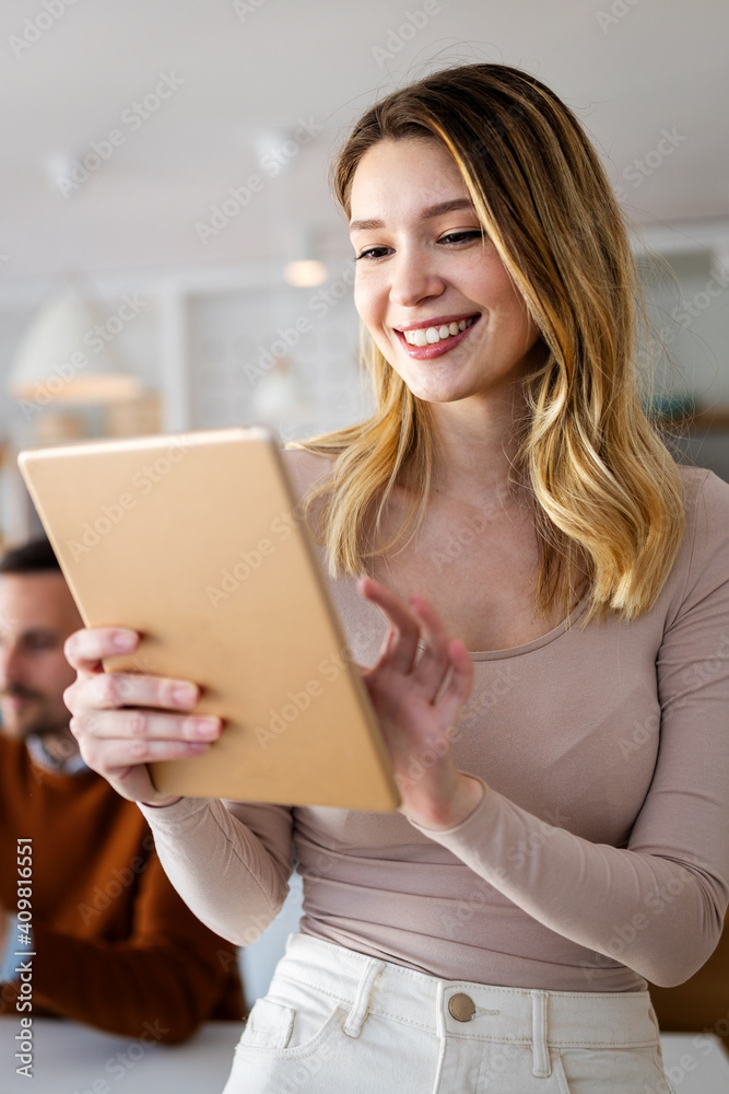 Beautiful young designer woman working on tablet in office. - obrazy, fototapety, plakaty