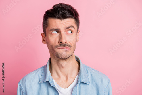Fototapeta Photo of displeased brunette young man look empty space bite teeth lips isolated on pastel pink color background obraz na płótnie