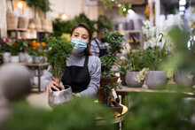 Portrait Of Skilled Woman Florist In Protective Mask Arranging Flowers In Pots At Flower Shop