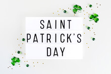 Lightbox With Saint Patricks Day Text, Shamrock Symbols Made Of Green Hearts And Stars Confetti On White Background. Flat Lay Irish Holiday Party Card Spring 17 March Lucky Clover Design