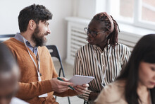 Multi-ethnic Group Of People In Audience At Business Conference Focus On Bearded Man Talking To African-American Woman While Sitting On Chairs