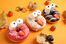 Delicious Donuts Decorated As Monsters On Orange Background. Halloween Treat