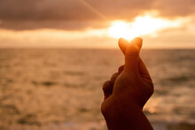 Concept Of Love The Hand Of The Person Making Up The Mini Heart Is Raised For A Picture With The Sunset Over The Sea.